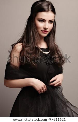 stylish elegant woman in black dress wearing pearls, studio shot - stock photo