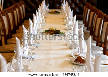 stylish empty glasses and plates at setting for guests at elegant table for wedding reception - stock photo