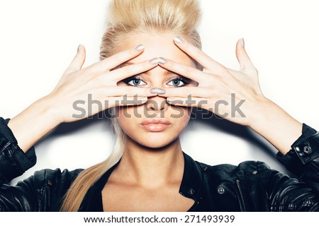 Stylish fashion blonde sexy young woman covered her face with her hand. Beauty girl in black clothes with bright makeup and hairstyle . White background, not isolated - stock photo