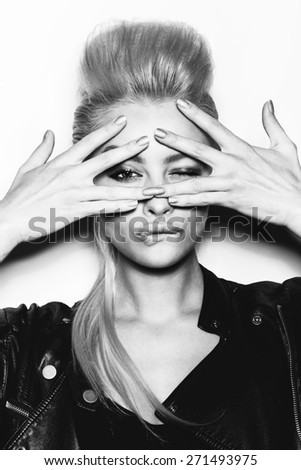 Stylish fashion blonde sexy young woman covered her face with her hand. Beauty girl in black clothes with bright makeup and hairstyle . Black and white toned. White background, not isolated - stock photo