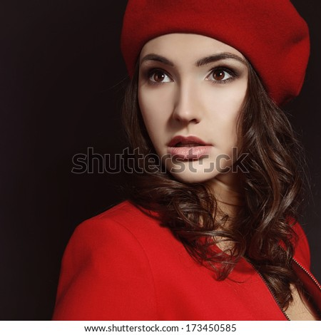Stylish fashion girl in red suit and beret with, posing at studio over black background - stock photo