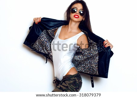 Stylish fashionable brunette girl hipster in black clothes.Leather jacket,sexy body,red lips,pathos,white background,not isolated.Fashion swag sexy woman having fun,going crazy,pretentious girl,tattoo - stock photo