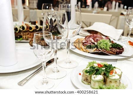 stylish fashionable decorated table with glasses and delicious food, celebration wedding, catering in the restaurant - stock photo