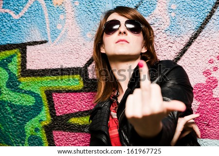 Stylish fashionable girl showing fuck off middle finger gesture against colorful graffiti wall. - stock photo