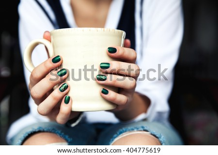 Stylish fashionable girl with a Cup of coffee and a green manicure in jeans. Fashion, care, beauty - stock photo