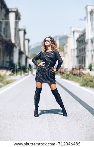 Stylish fashionable girl with brown hair,  stylish black dress and modern sunglasses posing in the center of the street. Fashion trendy woman concept