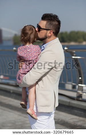 stylish father kissing daughter - stock photo