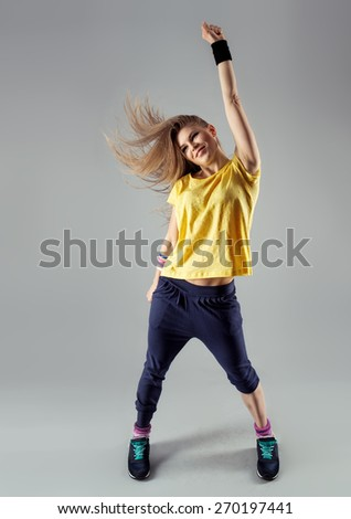 Stylish female hip hop dancer in dancing pose with disheveled hair posing in studio. Exercise, gym, sport.  Zumba Dance. - stock photo