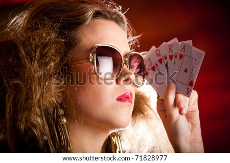 Stylish female poker player holding a royal flush - stock photo
