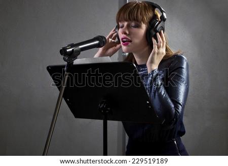 stylish female singer with microphone and reading lyrics - stock photo