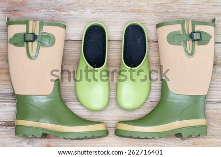 Stylish footwear for the garden with green rubber clogs and elegant matching green and beige gumboots in a symmetrical arrangement on a rustic wood background - stock photo