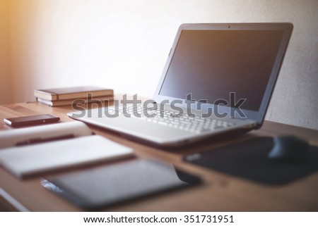 Stylish freelancer workspace with laptop open notepad work tools at home or studio office workplace. - stock photo
