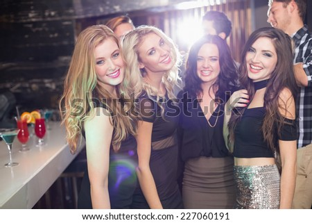 Stylish friends smiling at camera together at the bar