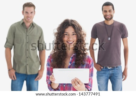 Stylish friends smiling at camera with one holding tablet on white background
