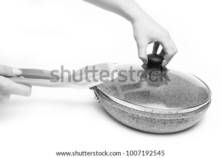 Stylish frying pan in hands on a white background