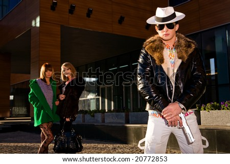 Stylish gangster with a gun and two young women on background outdoors - stock photo