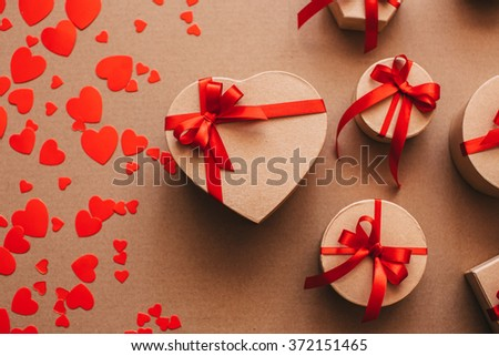 Stylish gifts with red ribbons and background of hearts. Top view.