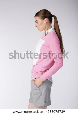Stylish Girl in Shorts Posing in Studio - stock photo