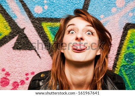 Stylish girl poking out her tongue to the camera against colorful graffiti wall. - stock photo