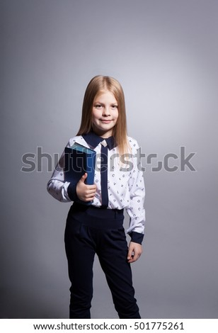 Stylish girl with the book on a gray background in the studio