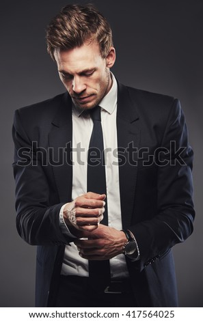 Stylish good-looking young businessman standing adjusting his cuff or cufflink on his shirt and suit jacket, upper body - stock photo