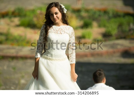 stylish gorgeous happy brunette bride  and elegant groom on the background of a park - stock photo