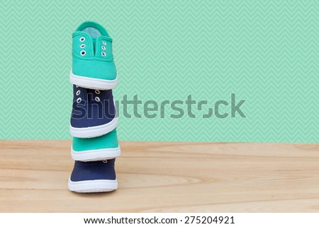 Stylish green and blue sneakers. A bunch of stylish shoe on the wooden floor over wallpaper with a stylish design - stock photo