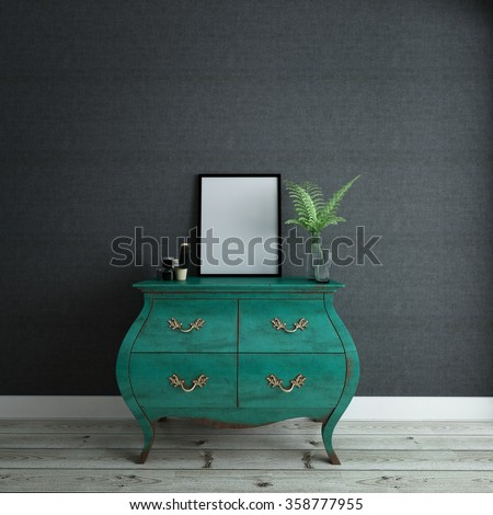 Stylish Green Dresser Drawers in Room with Gray Walls - Green Wardrobe with Picture Frame, Plant Vase and Knick Knacks in Sparsely Decorated Bedroom with Wood Floors and Copy Space - stock photo
