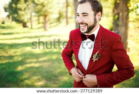 Stylish groom in tuxedo laughs suit marsala red, burgundy bow tie. Man buttoning his jacket outdoors. Professional hairstyle, beard, mustache. Wedding preparations, getting ready. Copy space for text. - stock photo