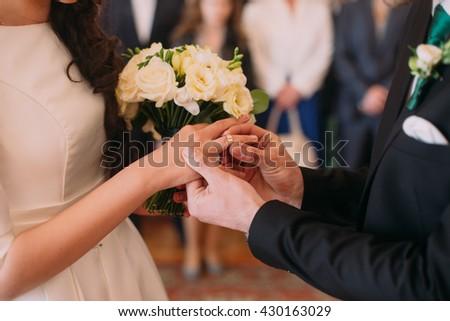 Stylish groom putting ring on finger of his elegant bride at wedding ceremony - stock photo