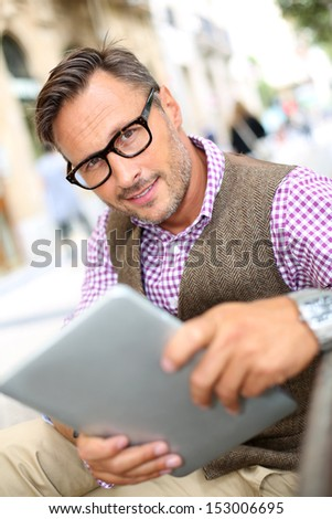 Stylish guy connected on internet with tablet in town