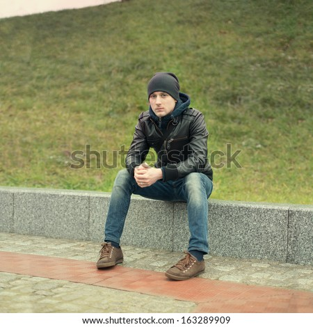 stylish guy relaxing in a city park - stock photo