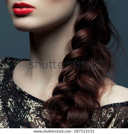 Stylish hairstyle concept. Portrait of beautiful young woman with great plait and perfect make-up posing over gray background. Healthy skin. Close up. Studio shot