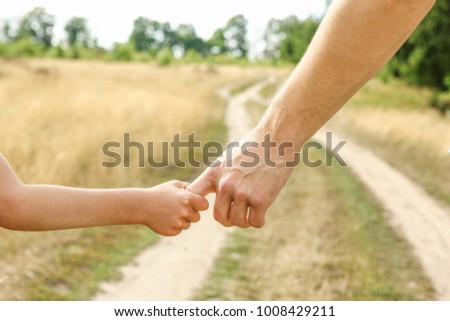 Stylish hands of a parent and child in the nature in a park background