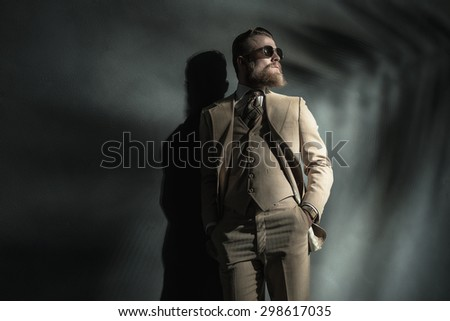 Stylish handsome bearded young man in a three piece cream suit standing leaning back against a grey wall with his hands in his pockets looking off to the side - stock photo