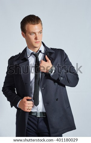 Stylish handsome businessman man in official clothing looking away. On a gray background.