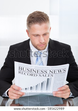 Stylish handsome businessman studying the financial newspaper or Business News while seated at his desk concentrating on the articles