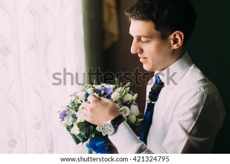 Stylish handsome dark haired groom holding a wedding bouquet standing near the window - stock photo