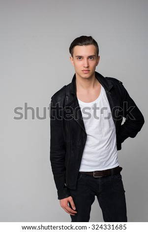 Stylish handsome guy is in black jacket. Portrait of fashionable young man with stylish haircut posing over white background. Perfect hair & skin.