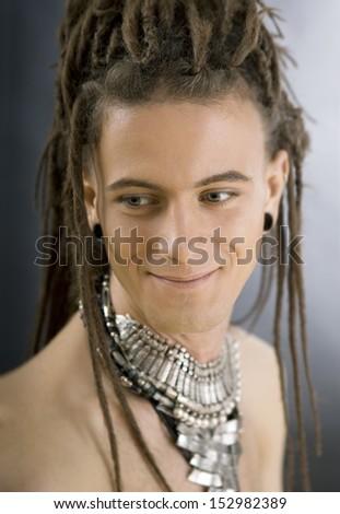 Stylish handsome guy with dreadlocks and jewelry - stock photo