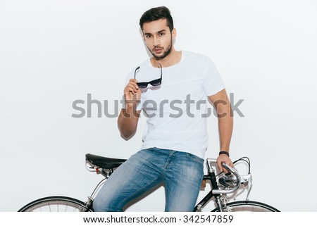 Stylish handsome. Handsome young Indian man leaning at his retro styled bicycle and looking at camera while standing against white background - stock photo