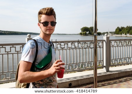 stylish handsome hipster man holding tasty cocktails, summer travel, space for text - stock photo