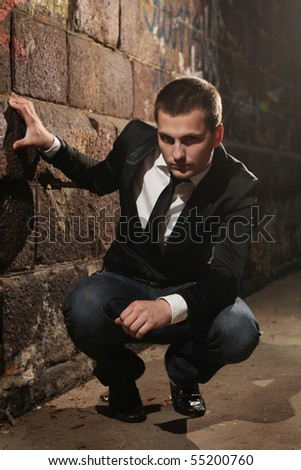 stylish handsome man sitting in dark tunnel - stock photo