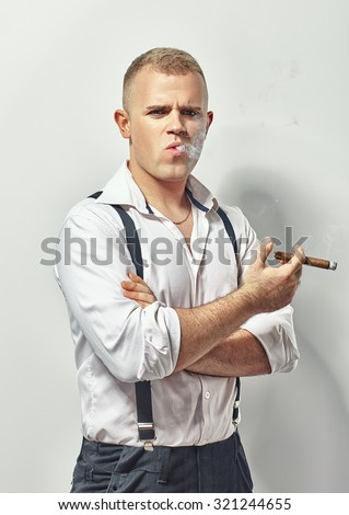 Stylish handsome man smoking cigar on white - stock photo
