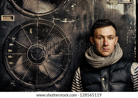 stylish handsome man with grey scarf standing against ventilators