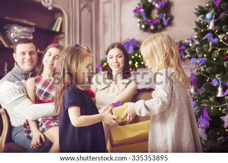 Stylish happy family celebrating christmas in room near the christmas tree - stock photo