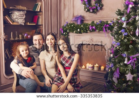 Stylish happy family celebrating christmas in room over christmas tree