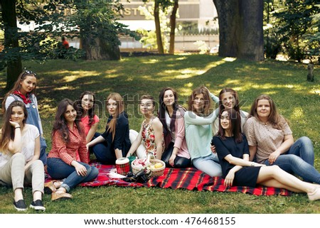 stylish happy group of women posing and smiling on picnic, sitting on blanket , joyful moments celebration in summer park