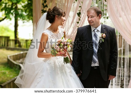 Stylish happy newlyweds on the wedding ceremony outdoors