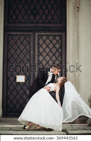 Stylish happy wedding couple on the background beautiful renaissance old castle. Romantic newlywed groom and bride.